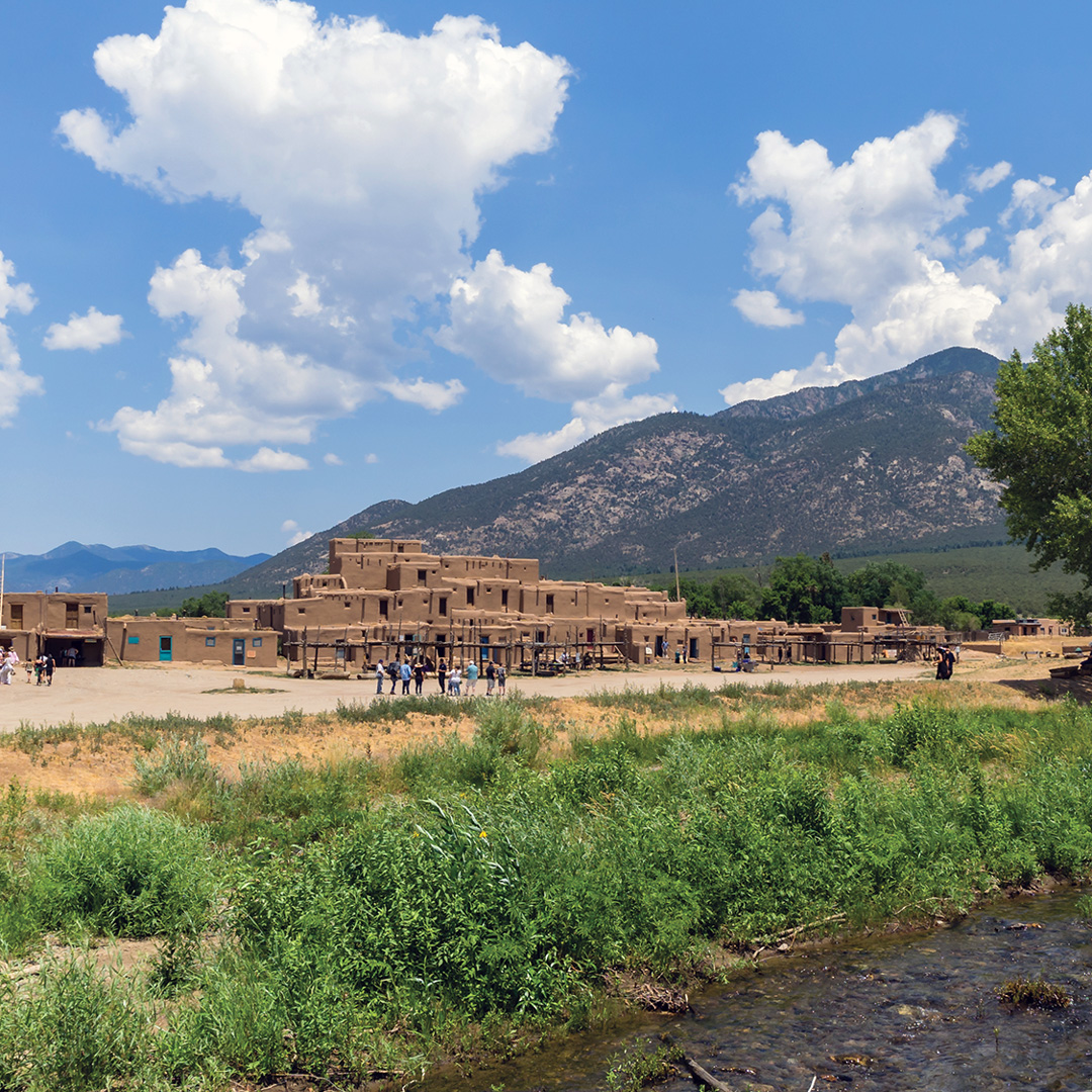 puebloan structures sit among the mountains and landscape of Taos