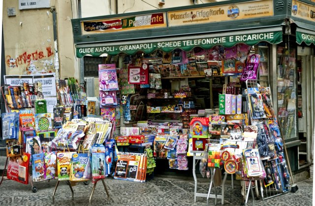 The space in front of a corner news stand is filled with racks of colorful magazines and toys for children.