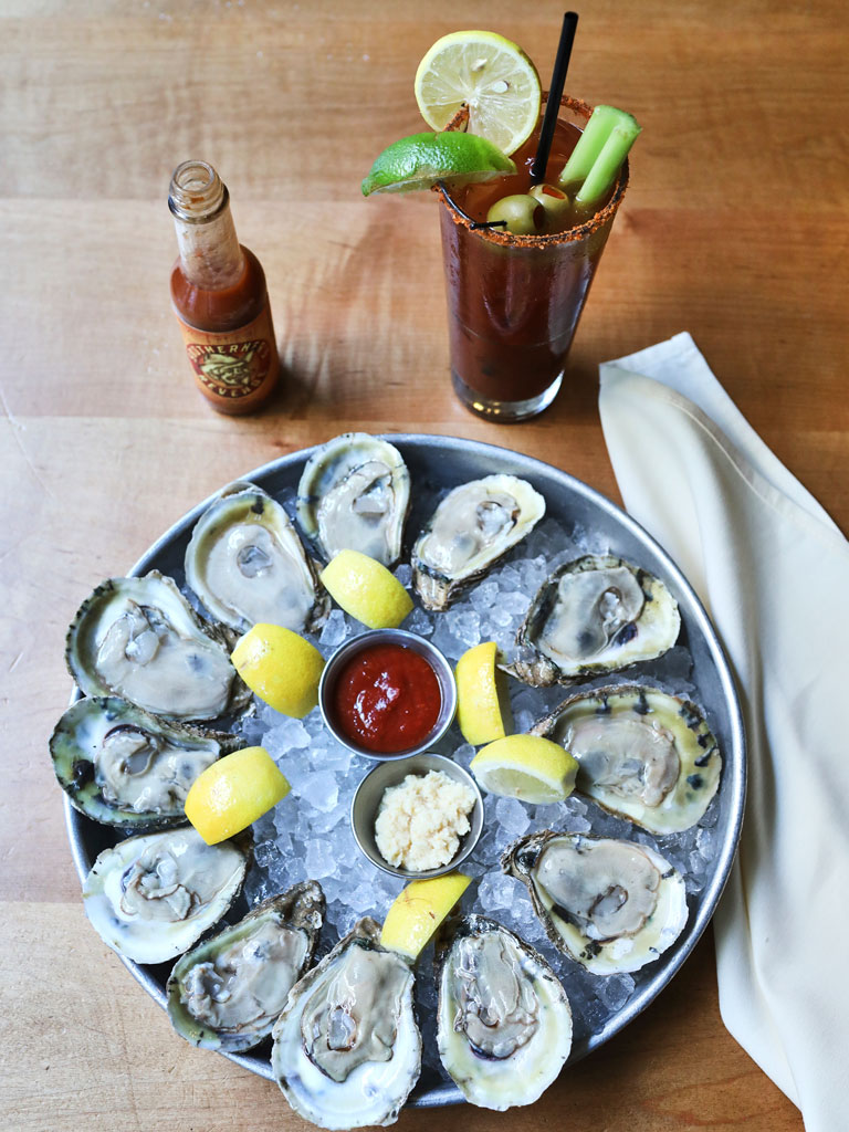 platter of oysters with a bottle of hot sauce and a bloody mary