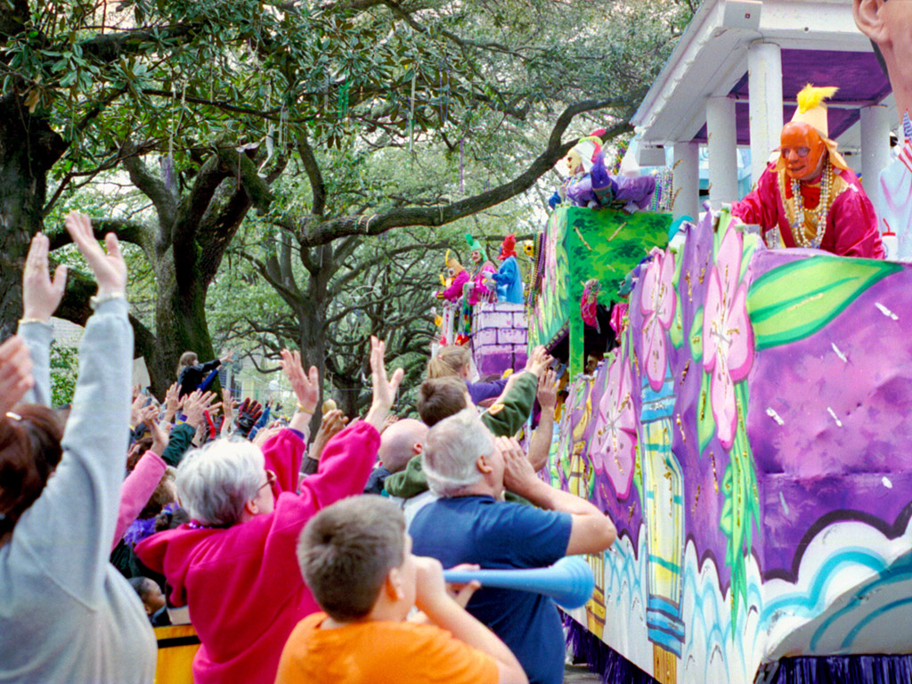 a crowd of people gathered to cheer and watch the Mardi Gras parade in New Orleans