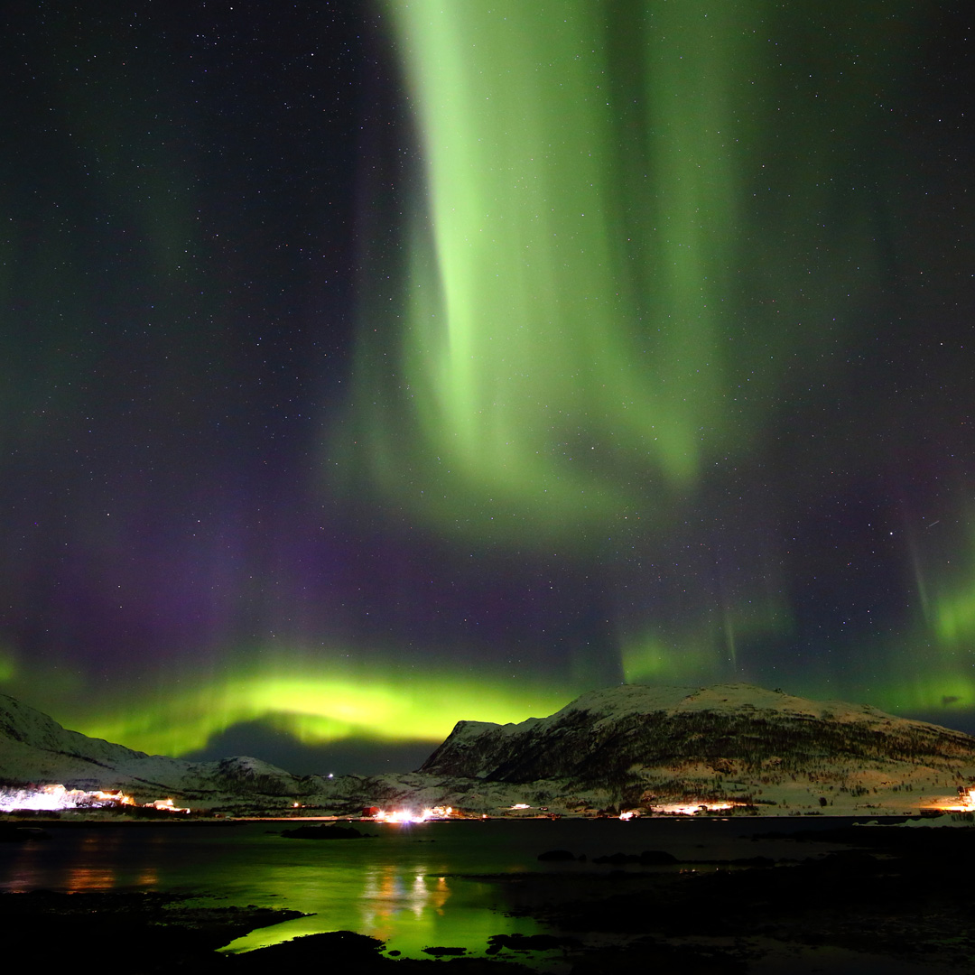 green aurora over the town of Tromso in Norway