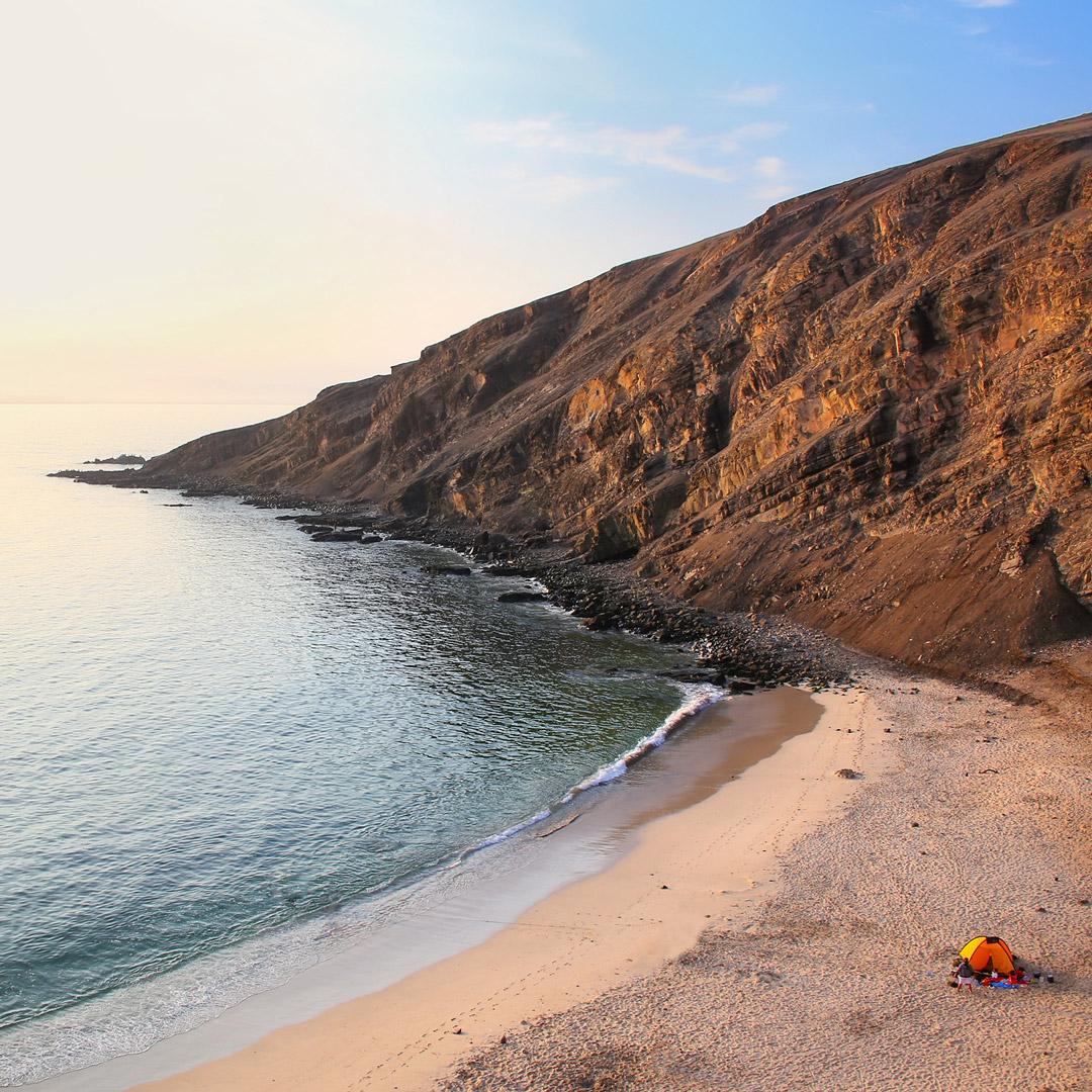 an orange tent sits on the beach near the ocean in Peru