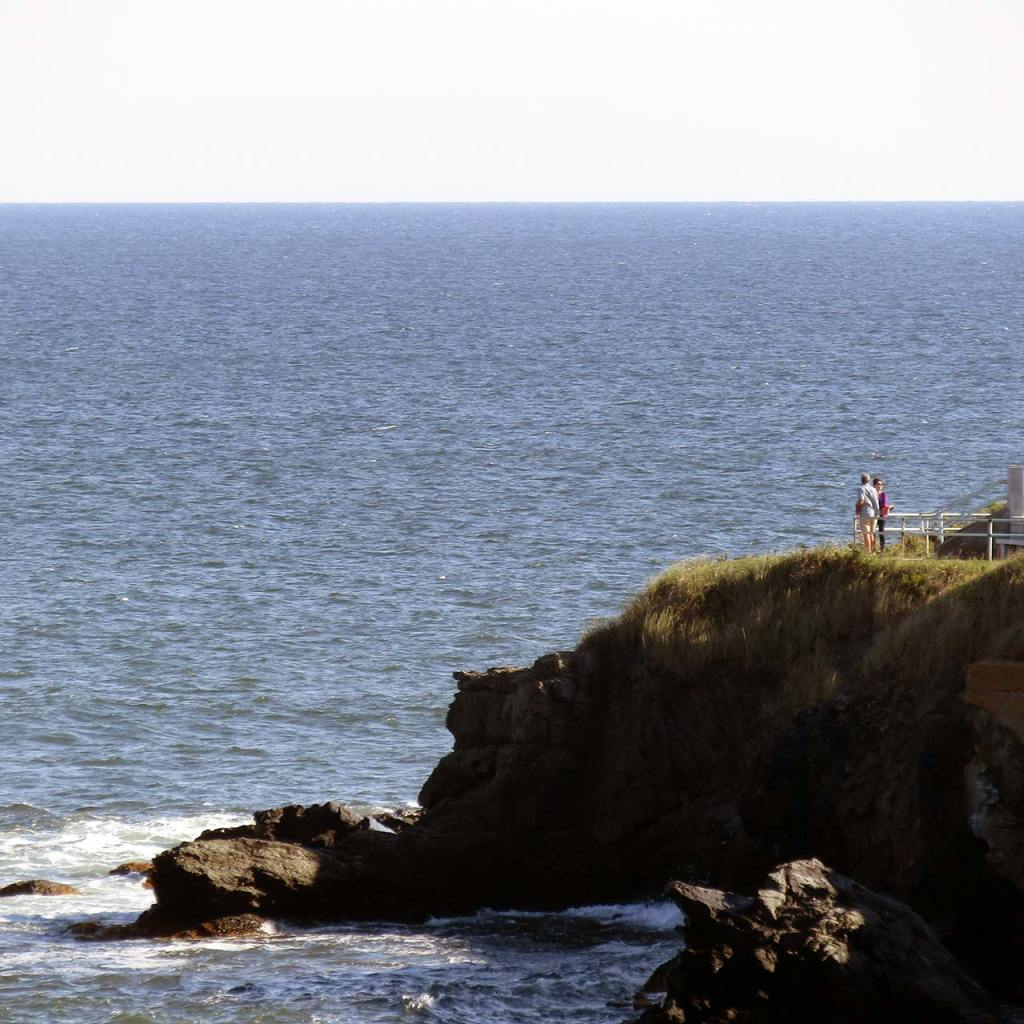 A couple stands at a rocky lookout point at Newport's Cliff Walk.