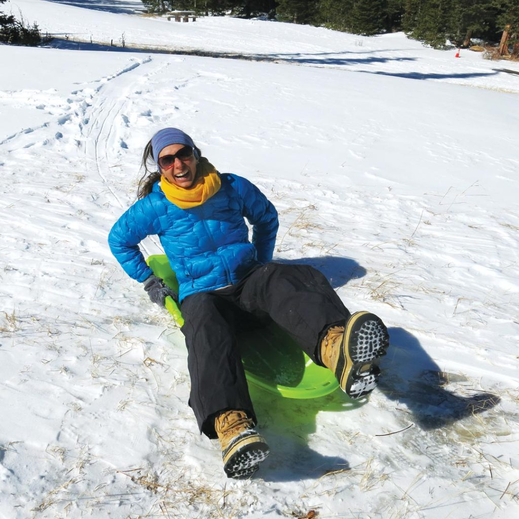 woman laughing while riding on a sled in snow