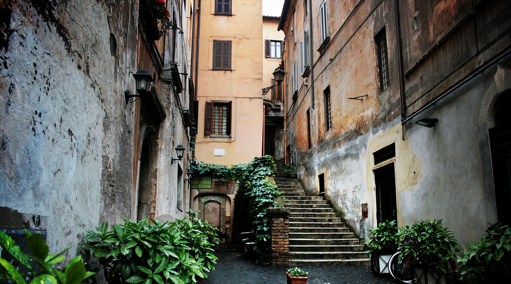 Plants and ivy line a narrow street in Rome with stone steps leading up to a second level between buildings.
