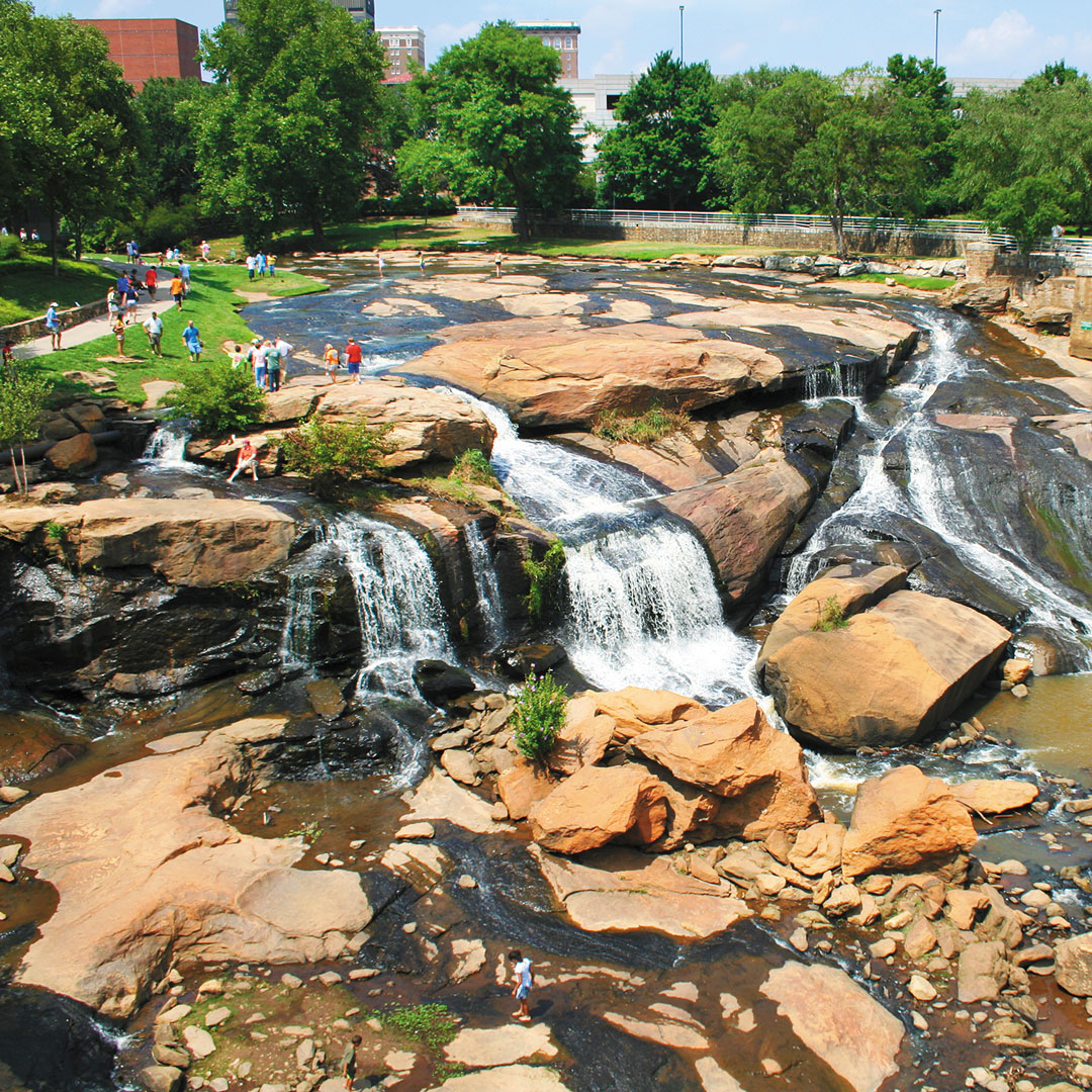 people playing in the water at Falls Park on the Reedy River