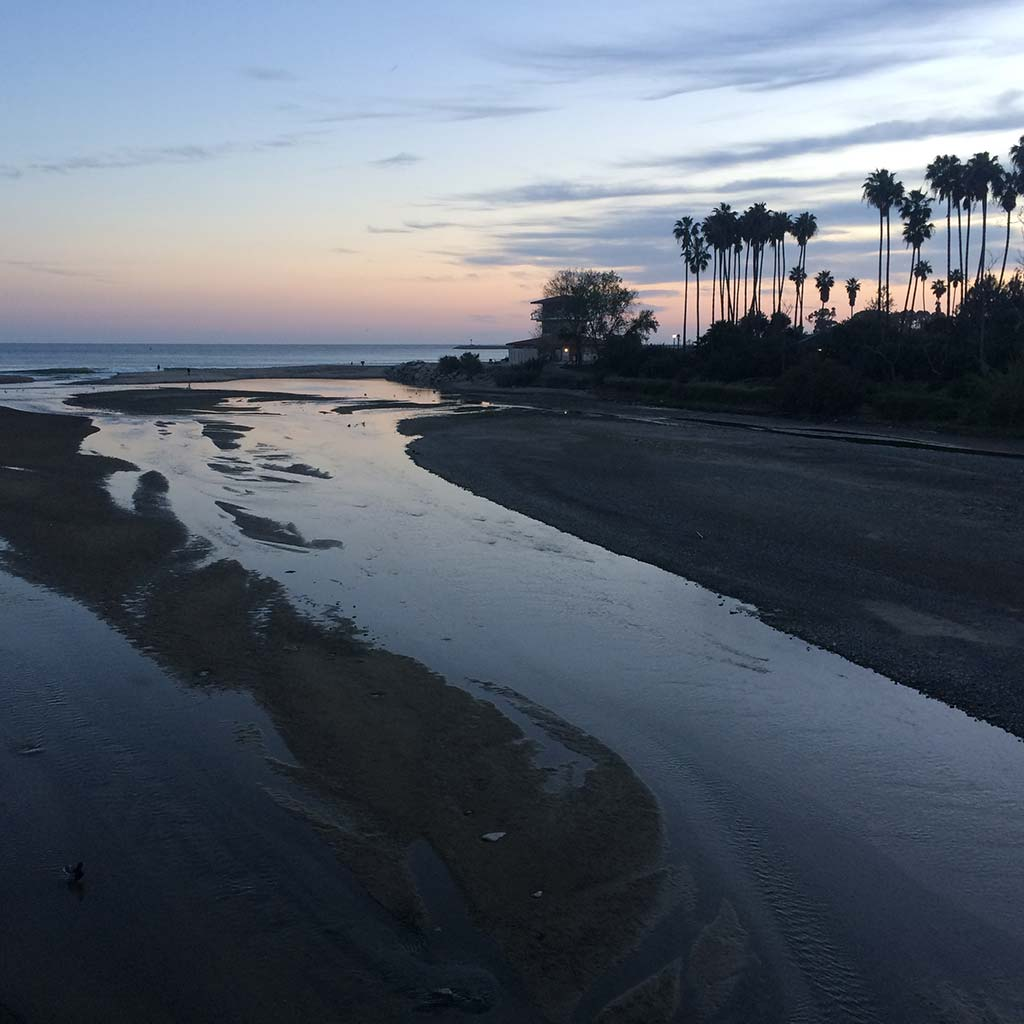 Doheny State Beach at sunset. Shallow waters come onto the sand and palm trees are visible in the distance
