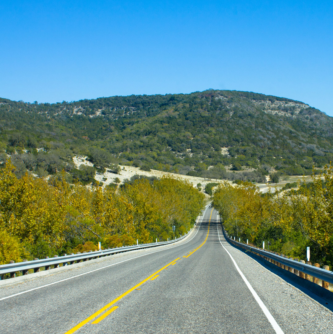 open road stretching toward scenic green hills in Texas