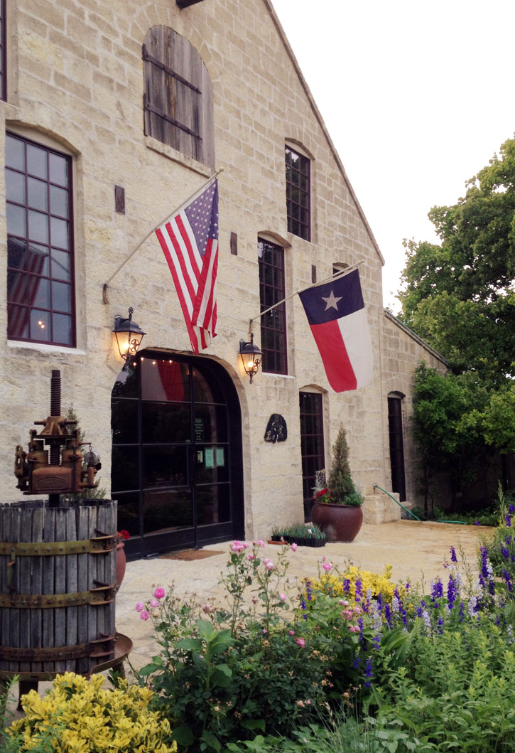 The state and US flag hang in front of rustic Becker Vineyards in the Hill Country.
