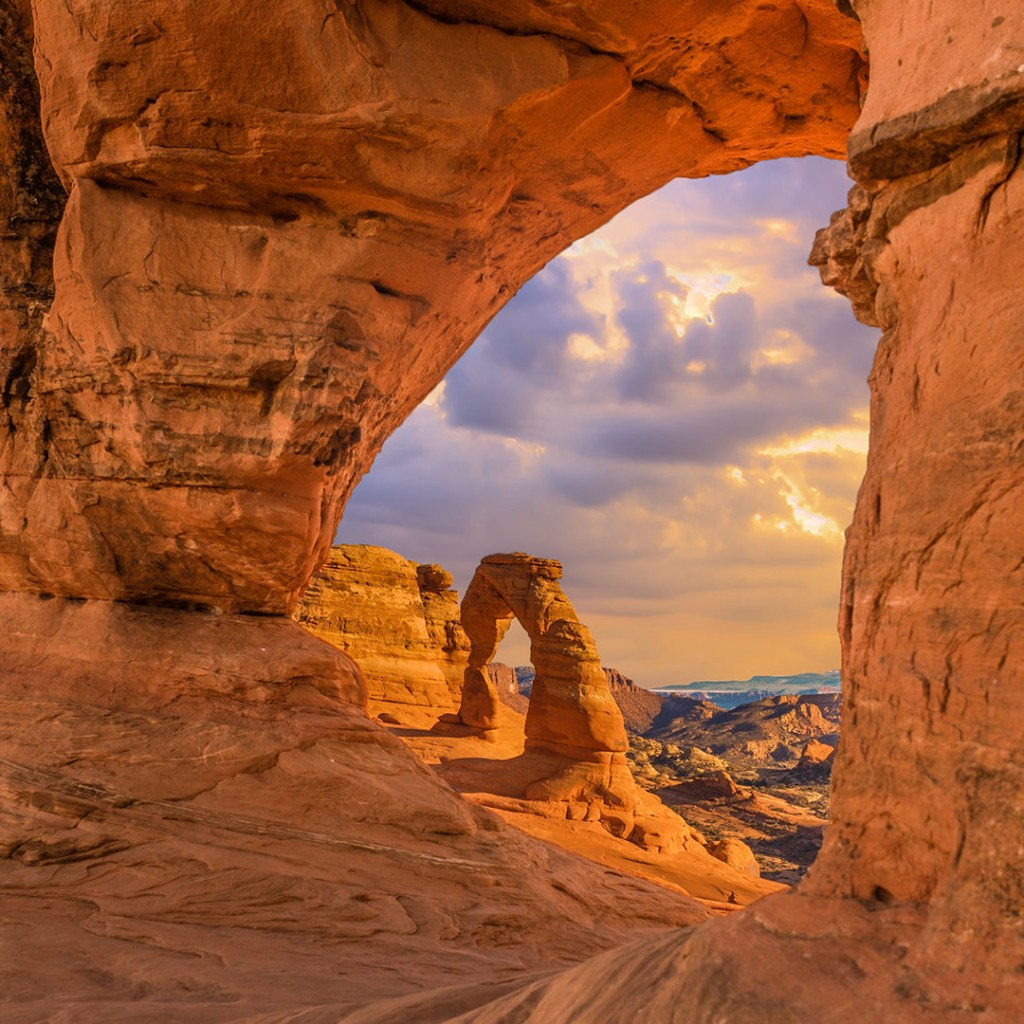 view through sandstone arches at sunset