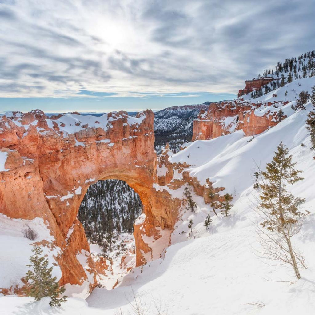 snow covering a natural bridge in bryce canyon national park