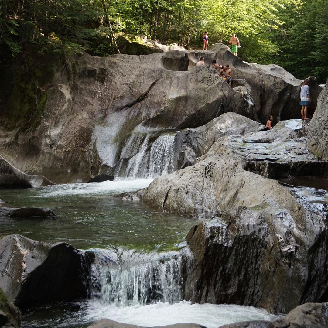 a cascade of waterfalls over big rocks