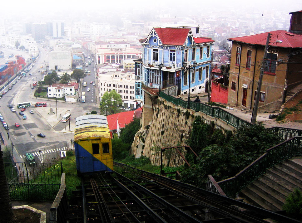 A funicular descends on its track beside a colorful hillside neighborhood.