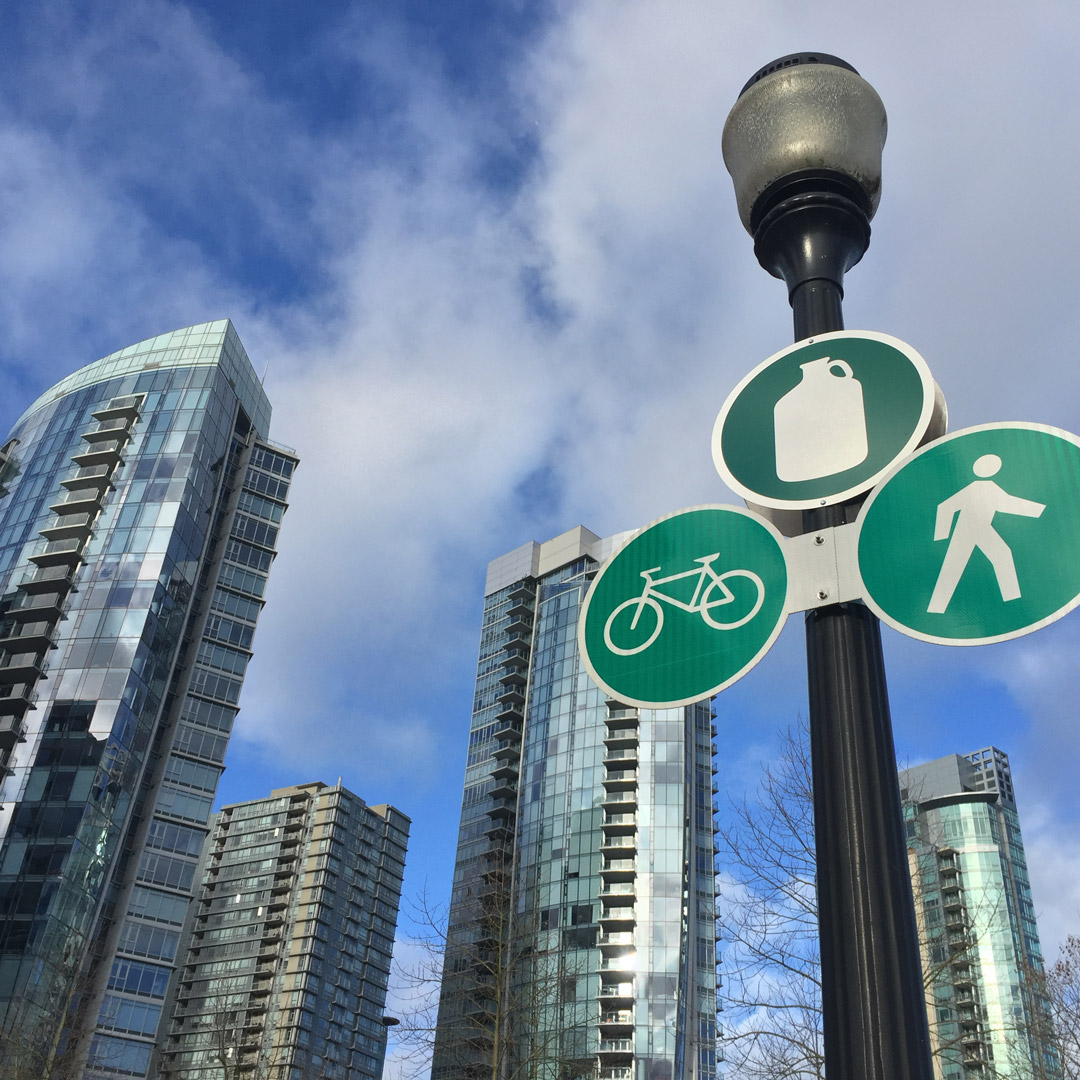 vancouver highrise buildings with a bike path crossing sign