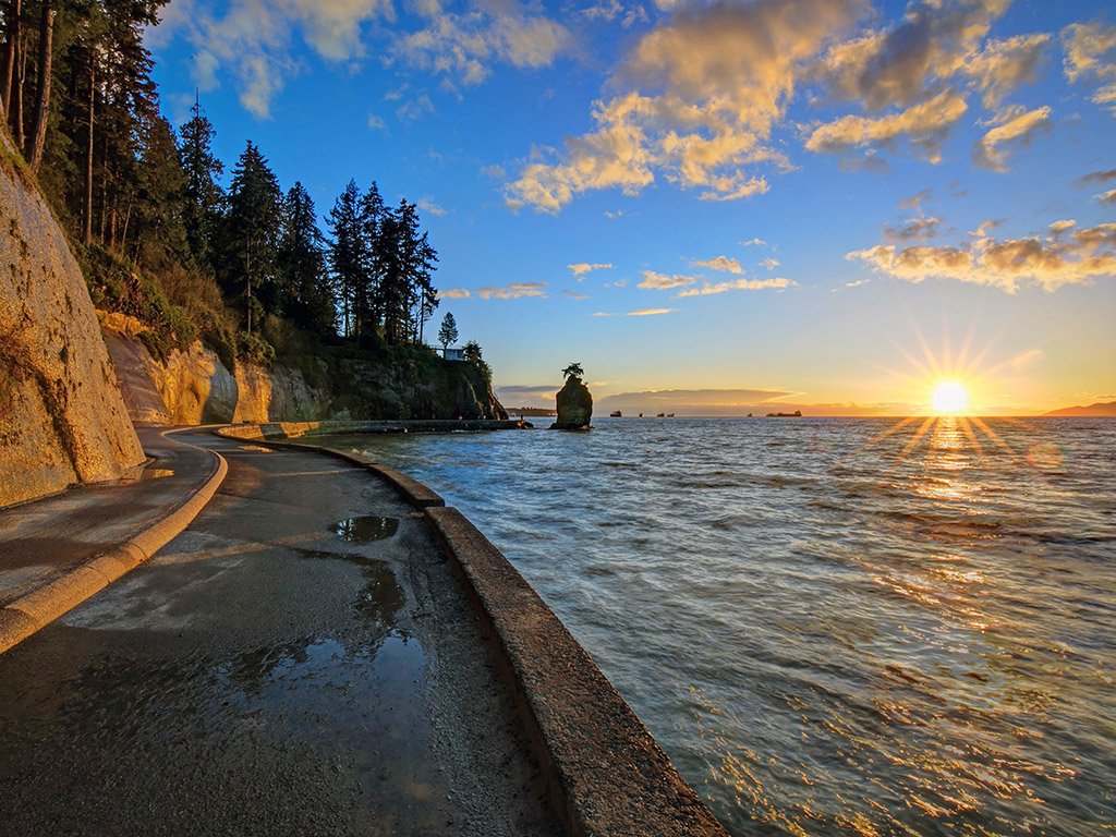 sunset on the water by the Stanley Park Seawall promenade in Vancouver