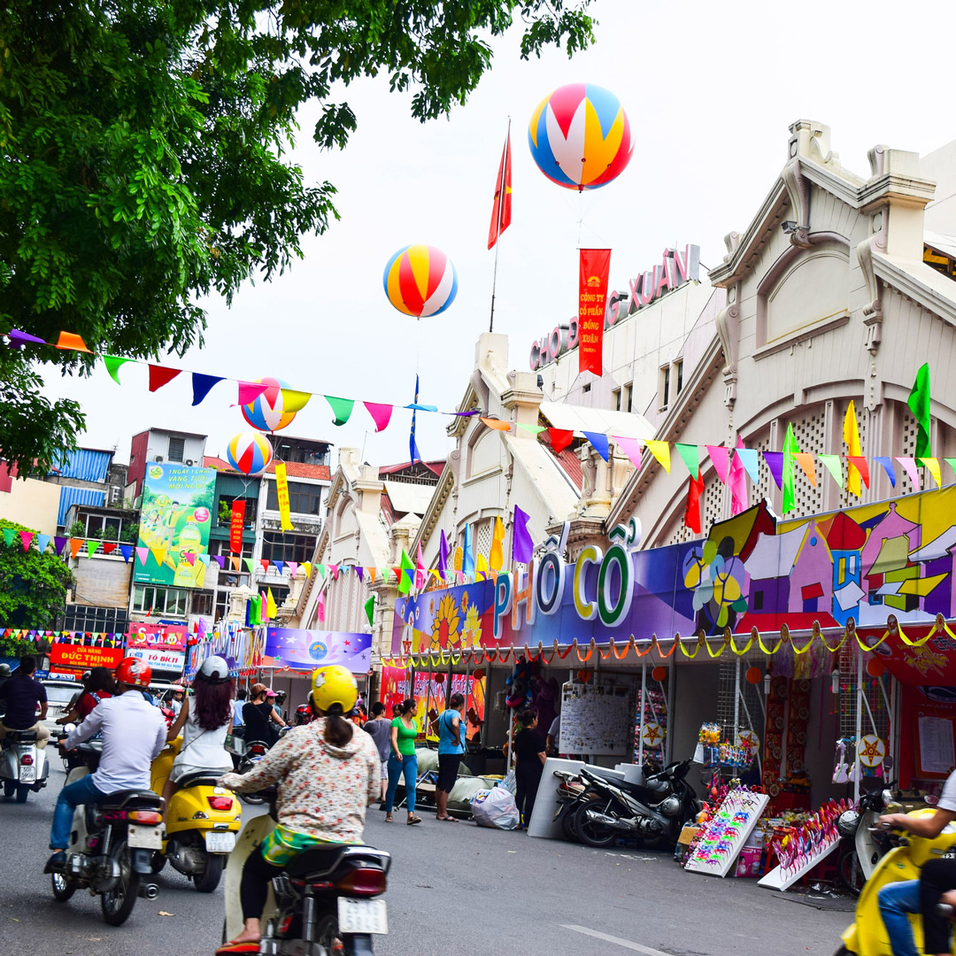 motorbikes riding by a colorful market in Hanoi