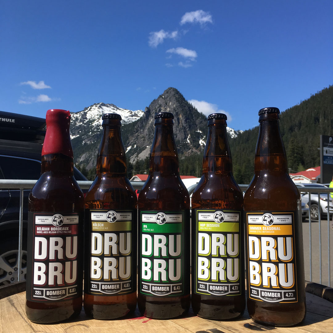 five bottles of beer sitting on a barrel with a mountain in the background