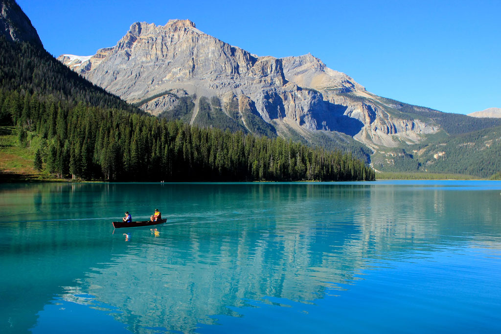 A canoe floats on the surface of Emerald Lake with the mountains reflected in the surface.