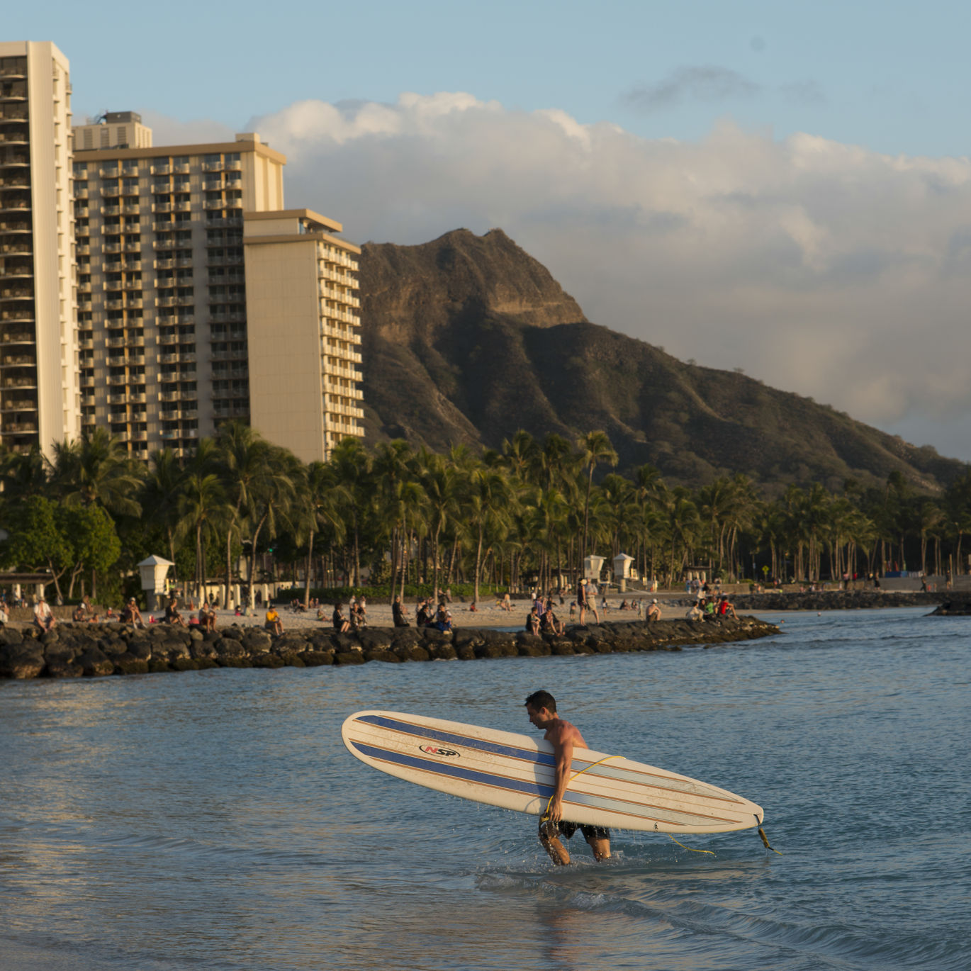 Diamond Head watches over a surfer coming in for the evening in Waikiki.