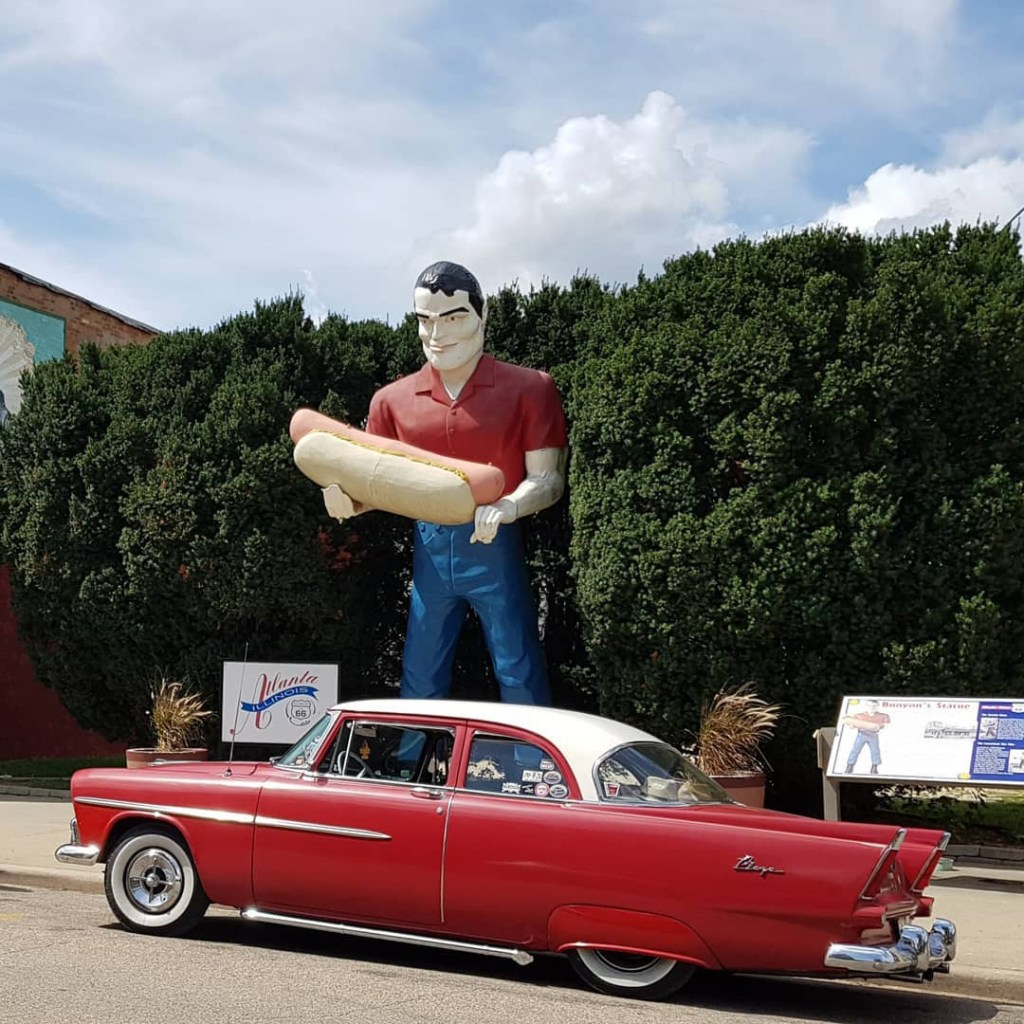 statue of a man holding a hotdog with a red classic car parked in front