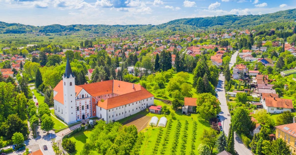Aerial view of the red-roofed, white buildings, set among the rolling green hills of Samobor, Croatia.