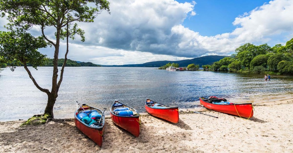 Four red kayaks resting on the sandy beach of Loch Lomond, Scotland.