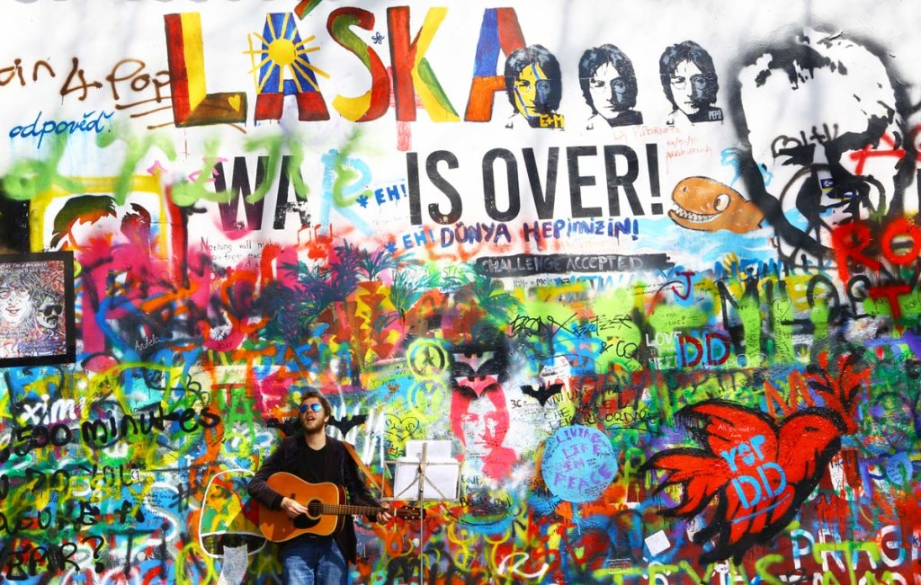 Man with a guitar playing in front of a brightly-painted graffiti wall.
