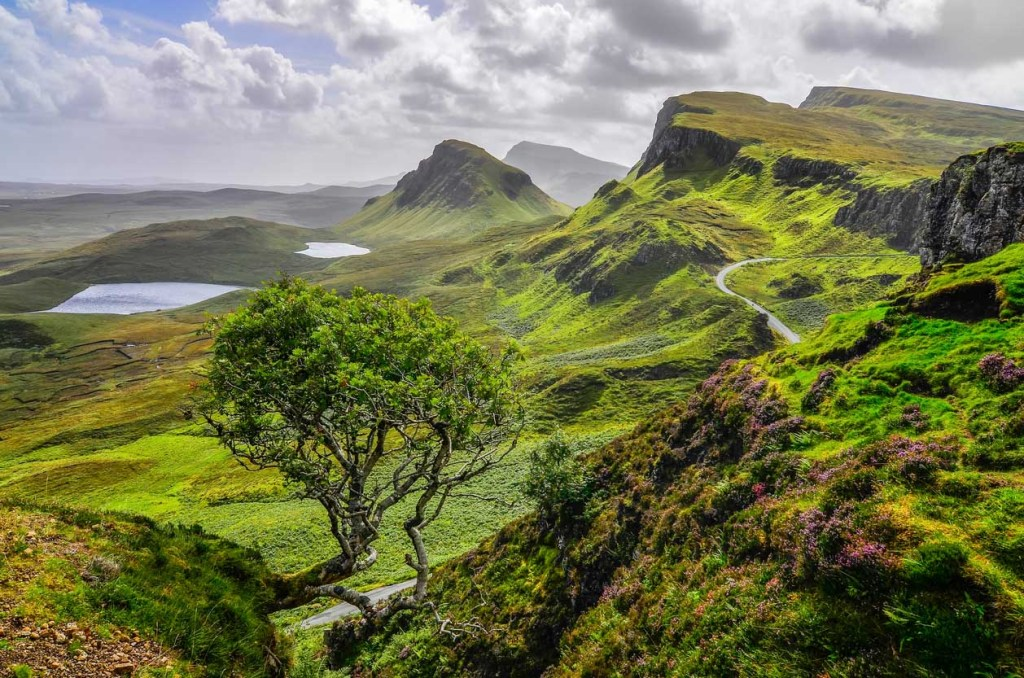 Narrow road passing through the green Quiraing mountains in Isle of Skye.