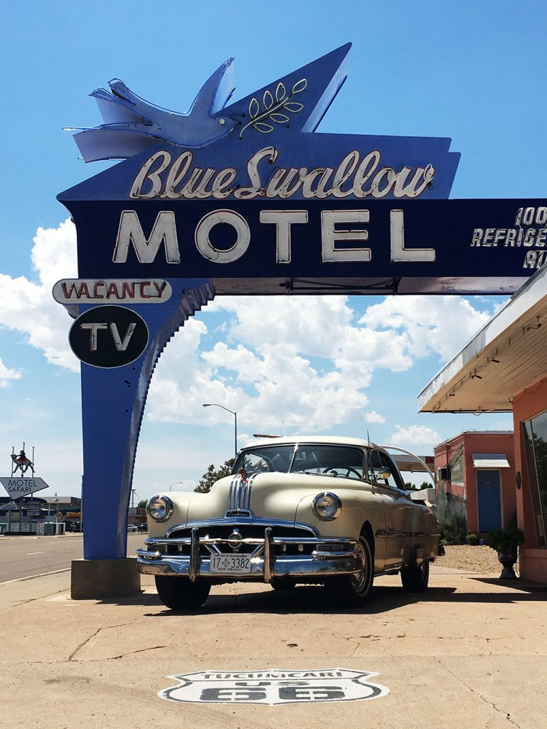 The recognizable classic Blue Swallow Motel sign in Tucumcari with a classic car parked beneath it.