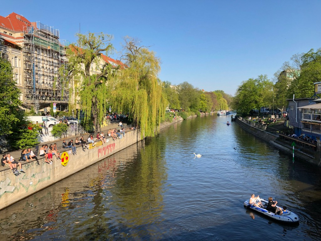 People enjoying sunny weather on the street, sitting at riverside in Berlin, Kreuzberg during spring