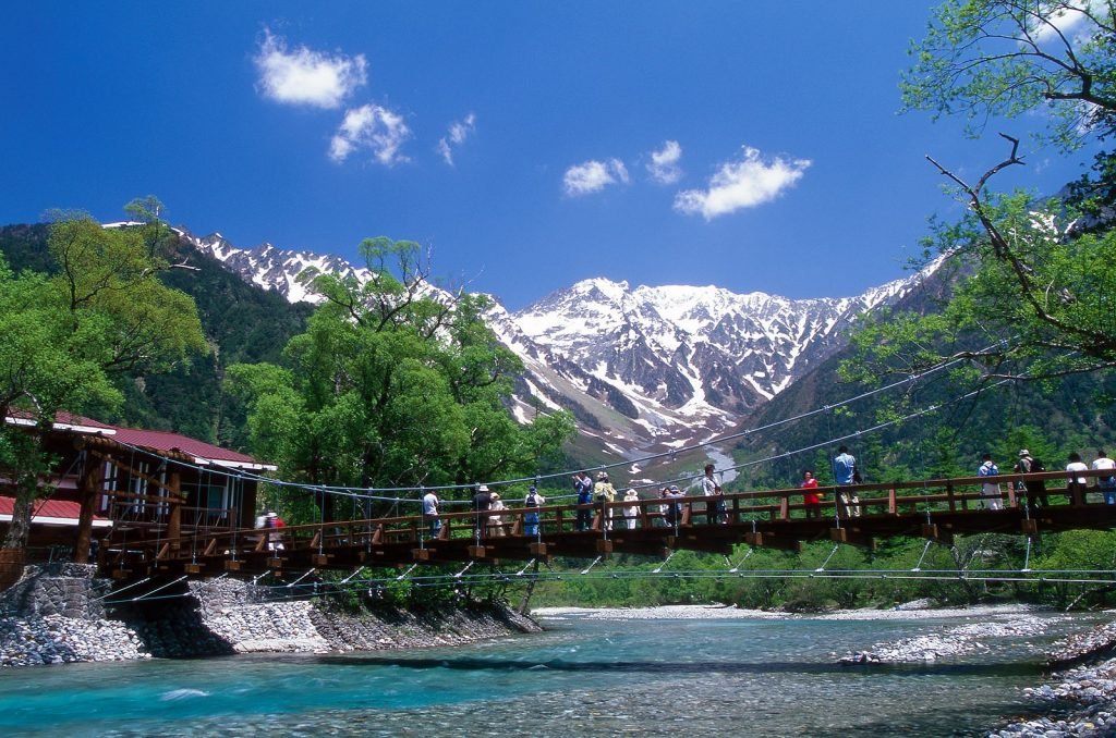 blue water under a bridge with a view of trees and mountains