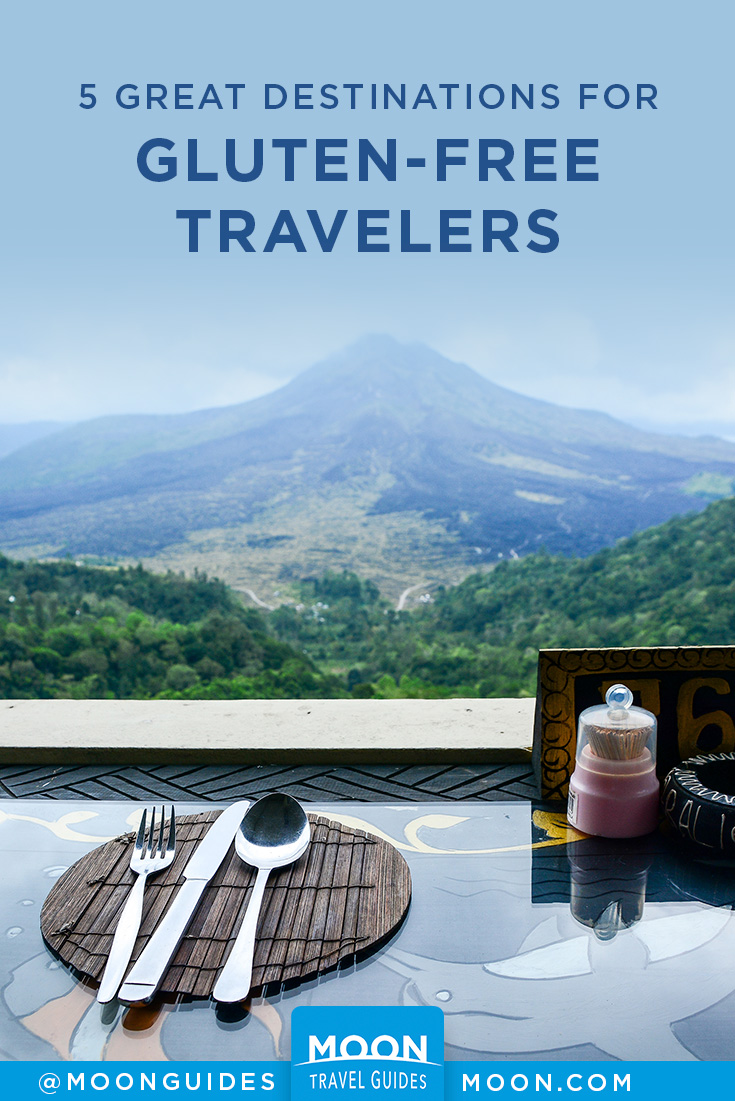 photo of a place setting at a table with a view of a volcano on a pinterest graphic for gluten free travel destinations