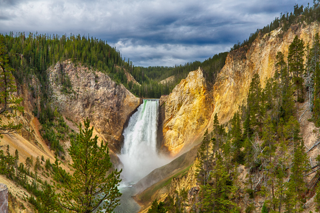 A waterfall running down the mountains in yellowstone national park.