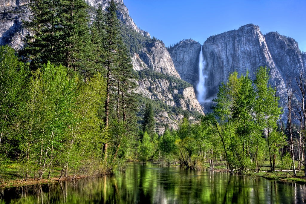 main stream at Yosemite Falls in Yosemite National Park with a reflective Merced River in the foreground.