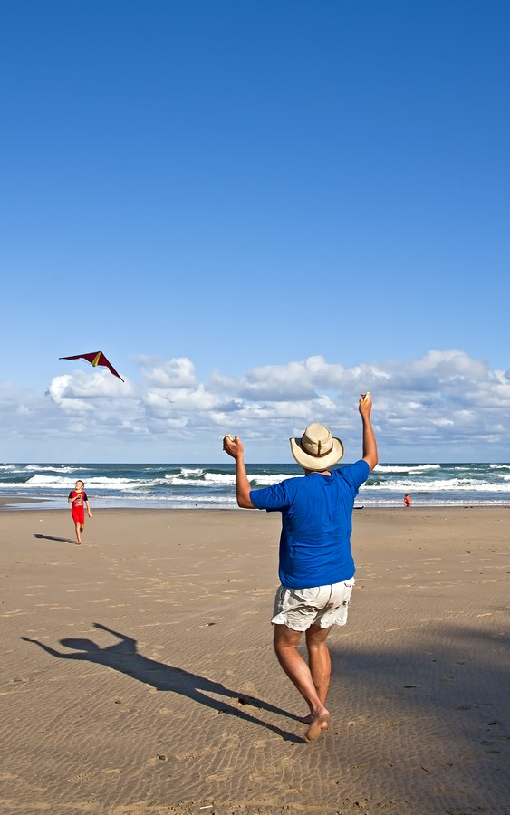 Little boy playing with kite and dad on the beach blue sky