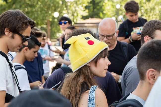 MILAN ITALY - AUGUST 7 2016: Hundreds of young people meet in a city park and take part in the Pokemon Go Tour official event for hunting and catching Pokemons.