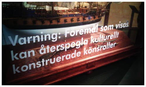 Fartygsmodell i monter med text: 'Varning: Föremål som visas kan återspegla kulturellt konstruerade könsroller'