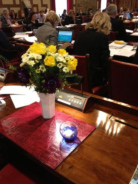 Birgittas bänk i kommunfullmäktige med blommor och ljus