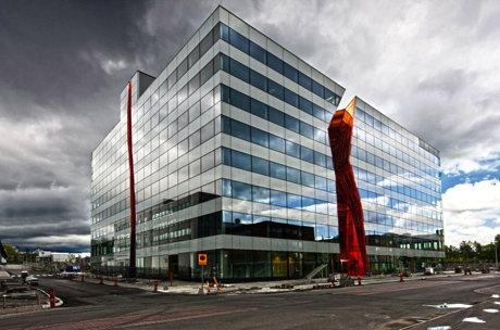kubiskt kontorshus i vitt och glas med vertikala 'sprickor' i rött och orange in i huset