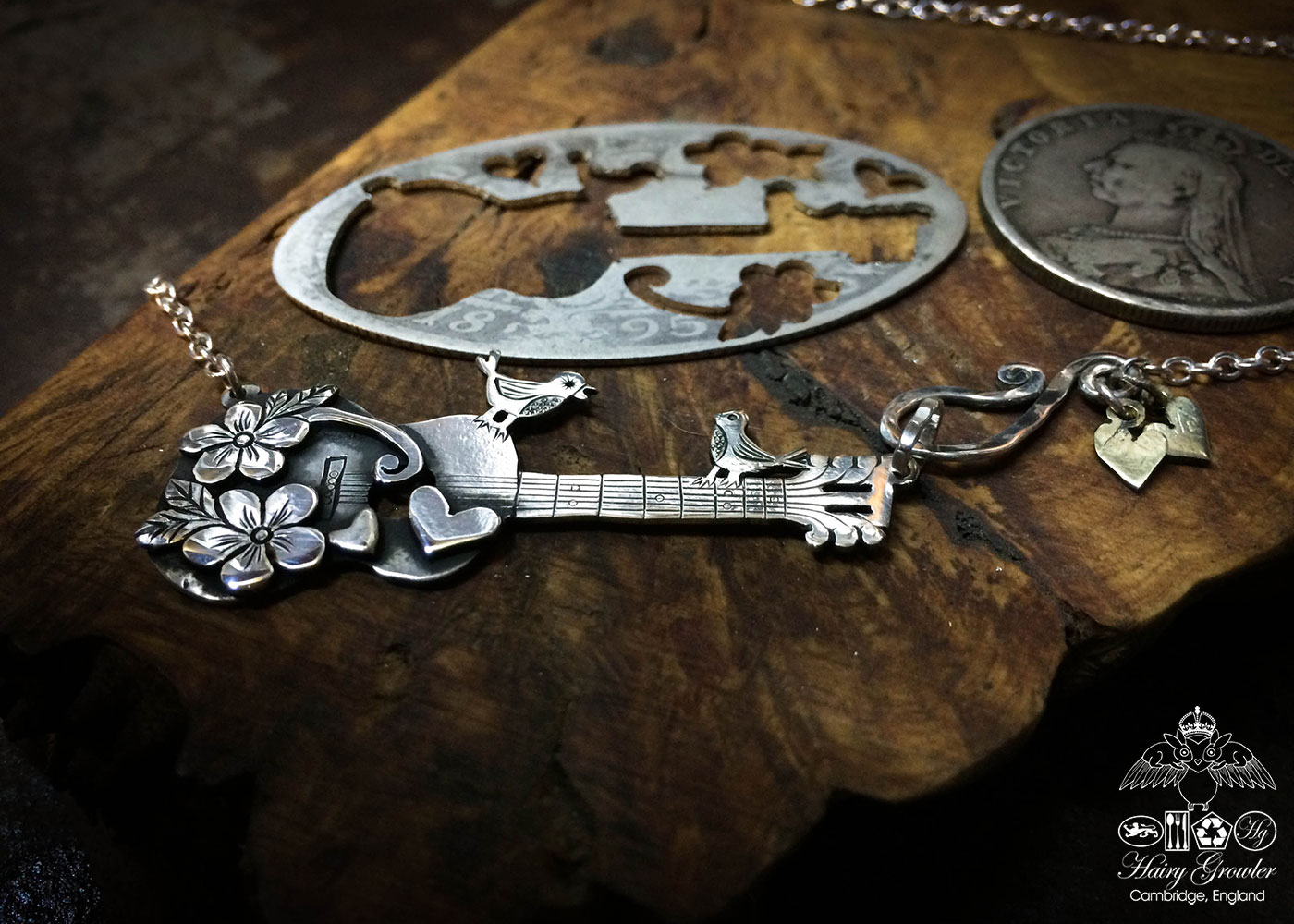 Handmade and upcycled sterling silver bird guitar necklace based on this silver Florin coin