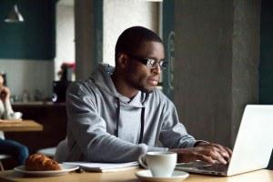 man using a atop computer at a table - man-using-a-;a[top-computer-at-a-table