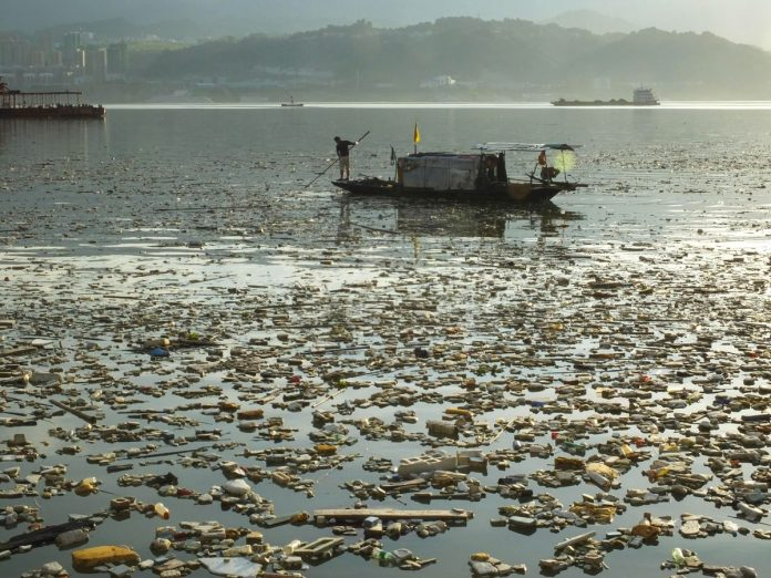A Chinese worker collects garbage floating on the Yangtze River