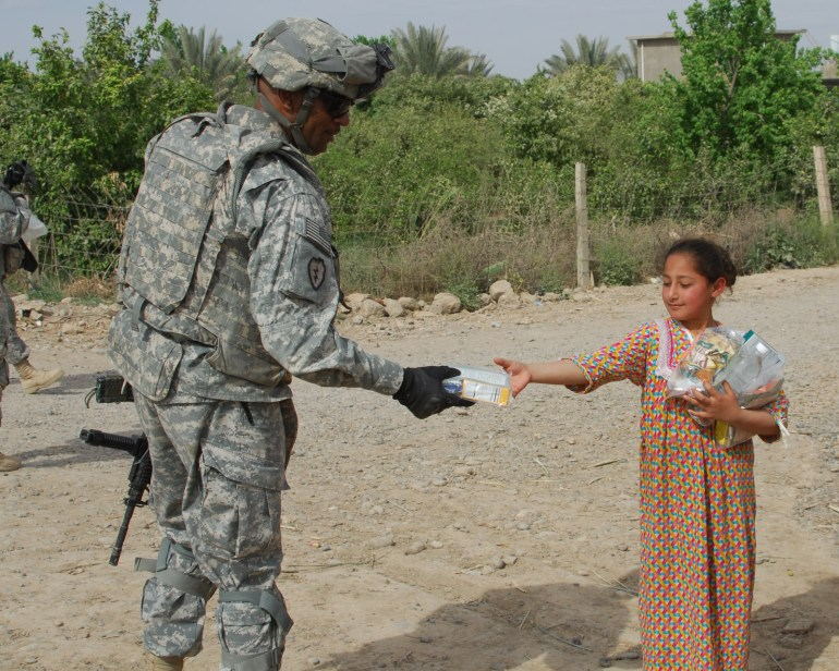Command Sgt. Maj. Thomas Jones Jr., command sergeant major, Headquarters and Headquarters Company, 2nd Battalion, 35th Infantry Regiment, 25th Infantry Division, hands a Halal meal to a young Iraqi girl in Bara'ia, Samarra, Iraq.