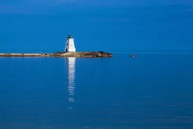 A lighthouse stands in relief from the brilliant blue waters of Haldimand County