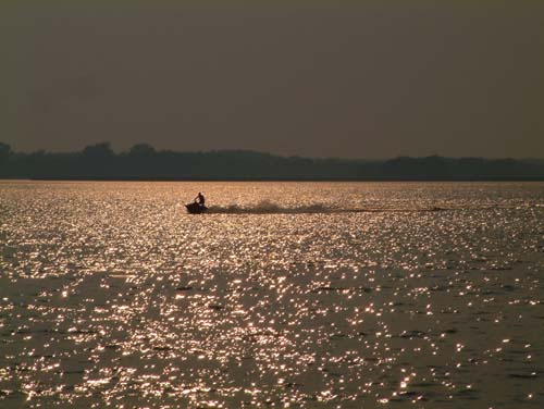 A jet skier enjoys a giddy thrill one more time during sunset on the Grand River