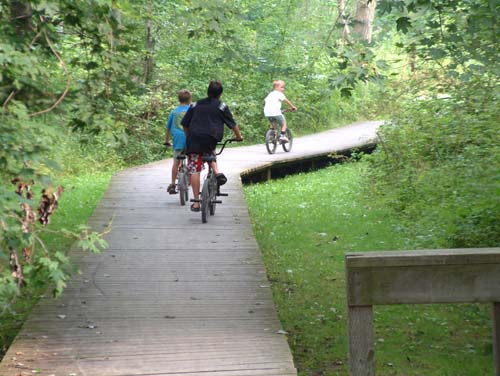 Three boys bike along a wood path in a forested area