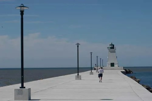A long white pier is lined with light posts that stand as silent sentries; a rustic lighthouse the crown jewel of the lake.