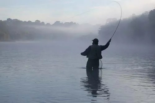 The silhouette of a fisherman during the early morning, casts his line line into the fruitful waters of the Grand River