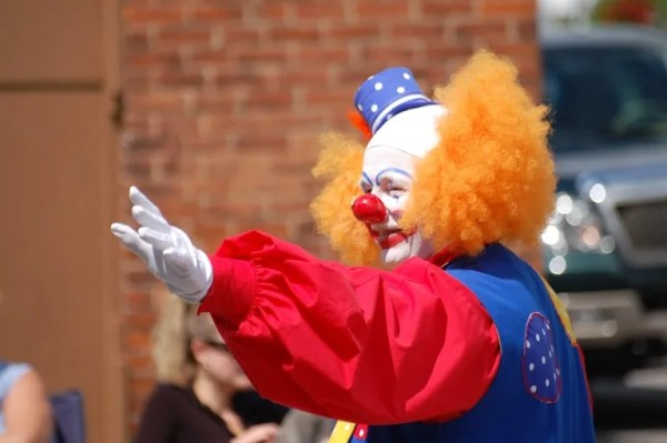 An image of a clown waiving happily during the 150th anniversary of Canada celebrated in Cayuga