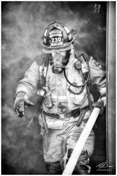 A firefighter emerges from a burning building; wisps of smoke clutching at him